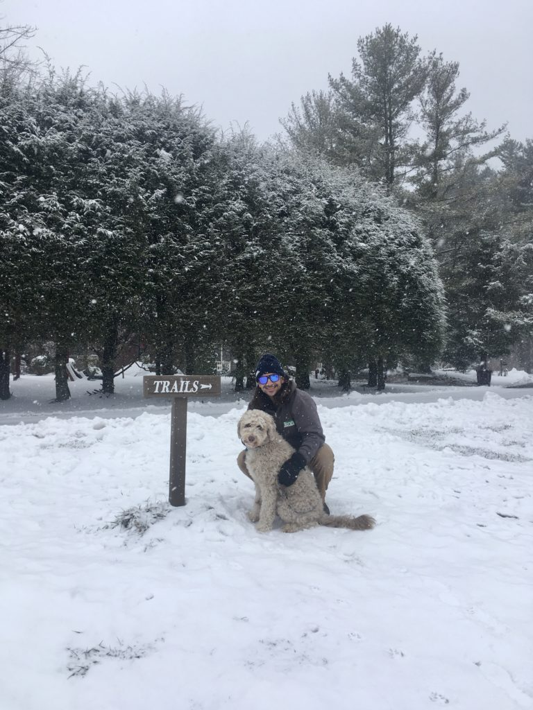 Man and dog posing in front of snowy trail sign
